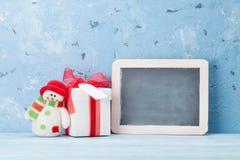 Pizarra de la Navidad, muñeco de nieve y caja de regalo Fotos de archivo libres de regalías