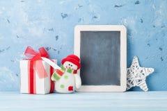 Pizarra de la Navidad, muñeco de nieve y caja de regalo Foto de archivo libre de regalías