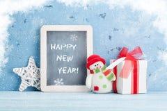 Pizarra de la Navidad, muñeco de nieve y caja de regalo Foto de archivo
