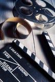 Pizarra de la película y rollo de película en la madera Foto de archivo libre de regalías