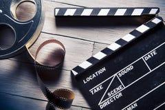 Pizarra de la película y rollo de película en la madera Fotografía de archivo