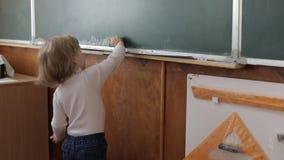 Pizarra de limpieza de la muchacha usando un toallita en sala de clase Proceso de la educación almacen de video