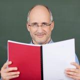 Pizarra de profesor Holding Book Against Fotos de archivo libres de regalías