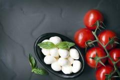 Pizarra del fondo de la comida con los tomates a de la vid de las bolas de la mozzarella del bebé imágenes de archivo libres de regalías