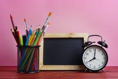 Pizarra, despertador y escuela inmóviles en cesta en Woode Fotos de archivo libres de regalías