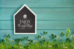 Pizarra e hierba formadas casa en la madera Fotografía de archivo libre de regalías