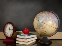 Pizarra en blanco con el globo, los libros y el reloj Imagen de archivo libre de regalías