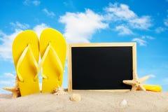 Pizarra en blanco con los accesorios de las estrellas de mar y de la playa en el beac Fotografía de archivo