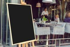 Pizarra en blanco del menú del restaurante con la gente blury Fotografía de archivo libre de regalías
