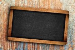 Pizarra en blanco en fondo de madera Imagen de archivo