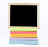 Pizarra en blanco en los libros coloreados Imágenes de archivo libres de regalías