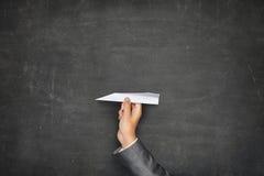 Pizarra en blanco negra con la mano que sostiene el papel Imagen de archivo