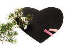 Pizarra en forma de corazón con las flores en la floración y las tizas rosadas aisladas en el fondo blanco fotos de archivo libres de regalías