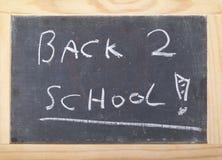 Pizarra en un marco de madera brillante que dice de nuevo a escuela Foto de archivo libre de regalías
