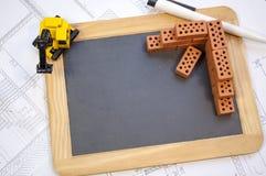 Pizarra en un plan o un modelo de la construcción, pequeños ladrillos de escoria y excavador foto de archivo