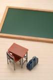Pizarra, escritorio, y bolso de escuela en la madera Imagen de archivo libre de regalías