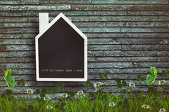 Pizarra formada casa en fondo de madera Imágenes de archivo libres de regalías