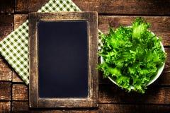 Pizarra negra para el menú y ensalada fresca sobre fondo de madera Imagenes de archivo