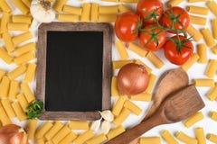 Pizarra y comida italiana Imágenes de archivo libres de regalías