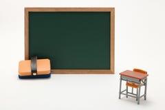 Pizarra y escritorio miniatura de la escuela en el fondo blanco Fotos de archivo libres de regalías
