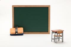 Pizarra y escritorio miniatura de la escuela en el fondo blanco Imagen de archivo