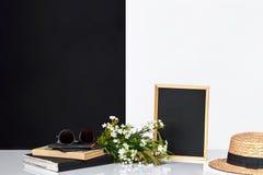Pizarra y libros en blanco en la tabla cerca de la pared blanca y negra Imagen de archivo libre de regalías