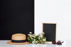 Pizarra y ramo en blanco de wildflowers en la tabla cerca de la pared blanca y negra Imágenes de archivo libres de regalías
