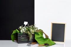 Pizarra y ramo en blanco de wildflowers en la tabla cerca de la pared blanca y negra Fotografía de archivo libre de regalías