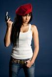 Pizca atractiva de la muchacha un arma un baret rojo Fotos de archivo libres de regalías