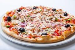 Pizza à l'oignon et le jambon, le fromage et la tomate Fond blanc Photographie stock libre de droits