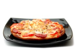Pizza. On a black plate Stock Photo