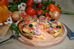 Pizza. A pizza and some ingredients Royalty Free Stock Image