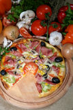 Pizza. A pizza and some ingredients Stock Photos