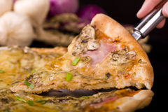 Pizza. A slice of pizza is lifted from the pan with a spatula royalty free stock image