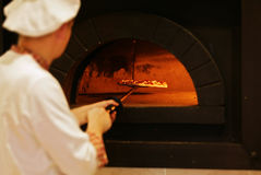 Pizza. The cook pulls out a ready pizza from the furnace royalty free stock photo