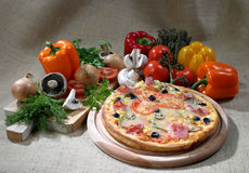 Pizza. A pizza and some ingredients Royalty Free Stock Photo