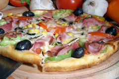 Pizza. A pizza and some ingredients royalty free stock photography
