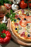 Pizza. A pizza and some ingredients Stock Photography