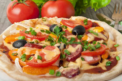 Pizza. Closeup of pizza with tomatoes, cheese, black olives and peppers Stock Photography