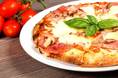 Pizza. With Ham and Mushrooms on the table with tomatoes Stock Photography