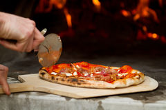Pizza. Slicing pizza by the outdoor wood burning oven Royalty Free Stock Image