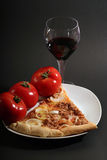 Pizza. With tomatoes a glass wine on a black background Stock Photo