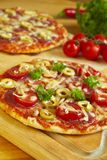 Pizza. Two pizzas and vegetables on wooden board Royalty Free Stock Photo