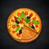Pizza affettata su fondo scuro Immagini Stock