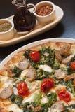 Pizza al forno di paesana e vassoio del condimento Immagini Stock