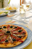 Pizza. With anchovies and olives on a blue dish Royalty Free Stock Photography