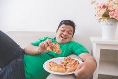 Pizza antropófaga excesso de peso preguiçosa ao colocar em um sofá imagens de stock royalty free