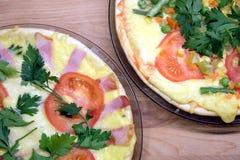 Pizza apetitosa com tomates, carne, milho e as ervilhas verdes em placas redondas na opinião superior do fundo de madeira Fotografia de Stock