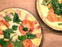 Pizza apetitosa com tomates, carne, milho e as ervilhas verdes em placas redondas na opinião superior do fundo de madeira Fotografia de Stock Royalty Free