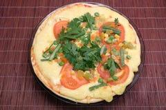 Pizza apetitosa con los tomates, el maíz y los guisantes verdes en la placa redonda en la opinión superior de la estera marrón de Imagenes de archivo